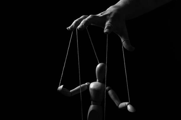 conceptueel beeld van een hand met koorden op vingers om een marionet in monochroom te controleren - exploitatie stockfoto's en -beelden
