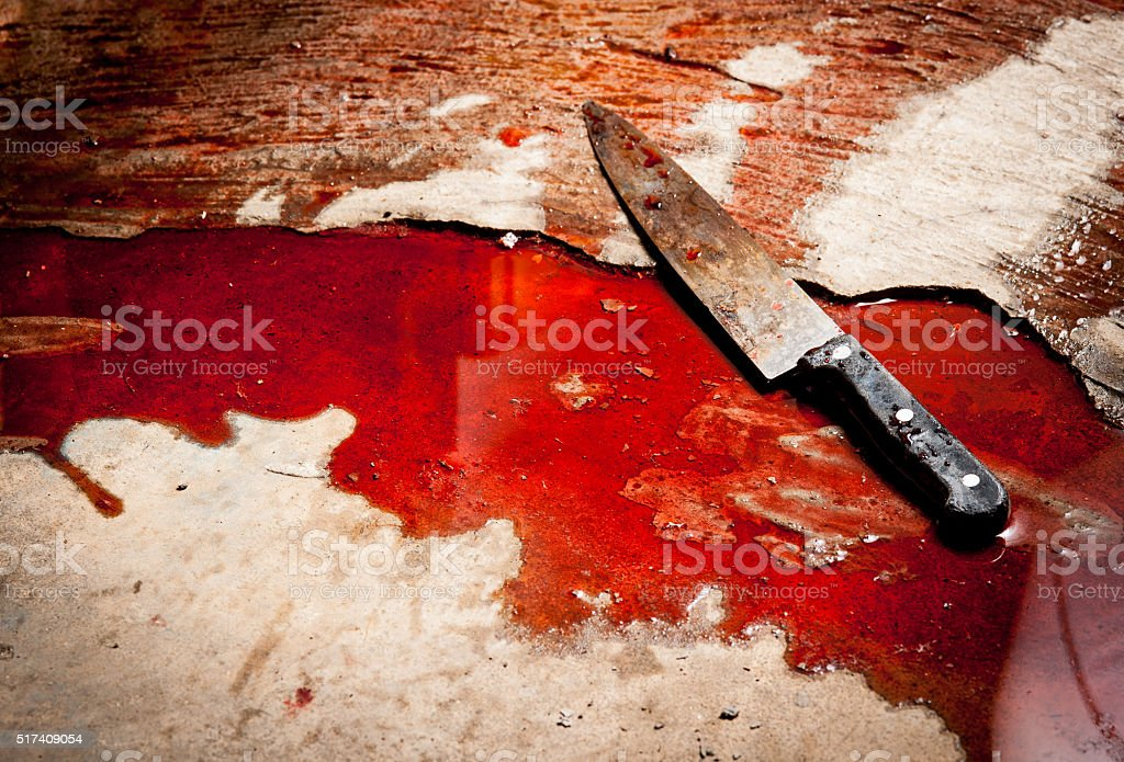 Conceptual image of a sharp knife with blood on floor stock photo