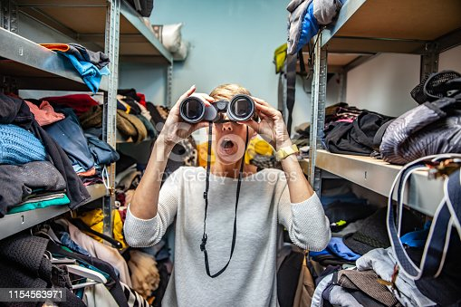 Conceptual image of a Woman using Binoculars to Find Clothing in the messy Closet