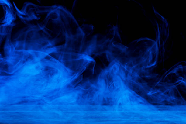 Conceptual image of blue smoke isolated on dark black background and wooden table. Conceptual image of blue smoke isolated on dark black background and wooden table. smoke physical structure stock pictures, royalty-free photos & images