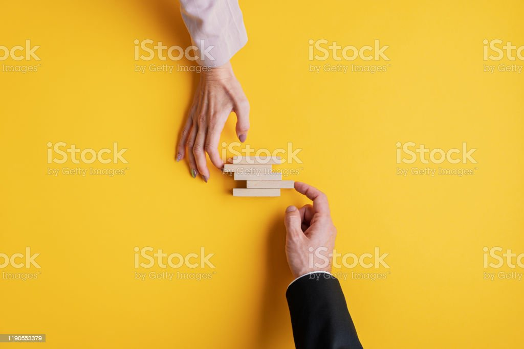 Conceptual image of business stability and teamwork Hands of a businessman and businesswoman stacking wooden pegs in a conceptual image of business stability and teamwork. Adult Stock Photo