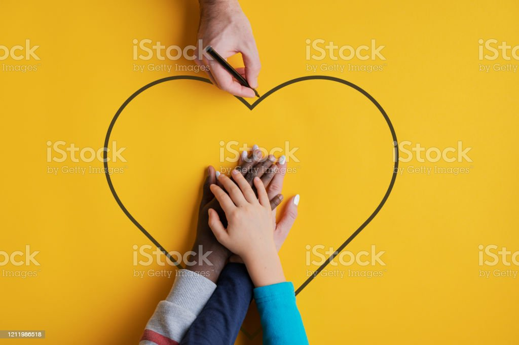 Conceptual image of family and unity Top view of a man drawing heart shape around stacked hands of his family - fife and two kids, one caucasian one black in a conceptual image. Over yellow background Adoption Stock Photo