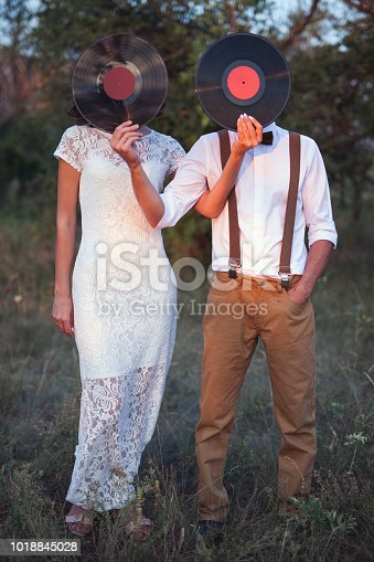 istock Conceptual Image of Man And Woman Hold A Vinyl Record Discs On Their Faces 1018845028