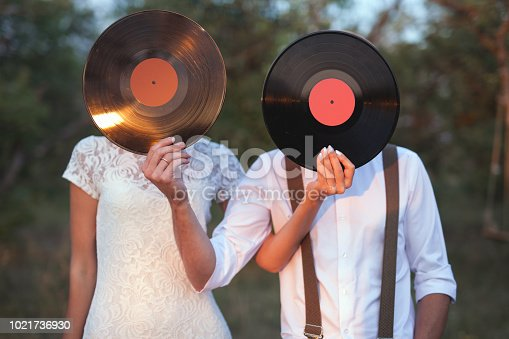 istock Conceptual Image of Man And Woman Hold A Vinyl Record Discs On Their Faces 1021736930