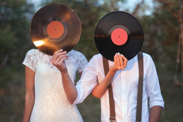 konzeptbild von mann und frau halten einen rekord schallplatten auf ihren gesichtern - hipster braut stock-fotos und bilder