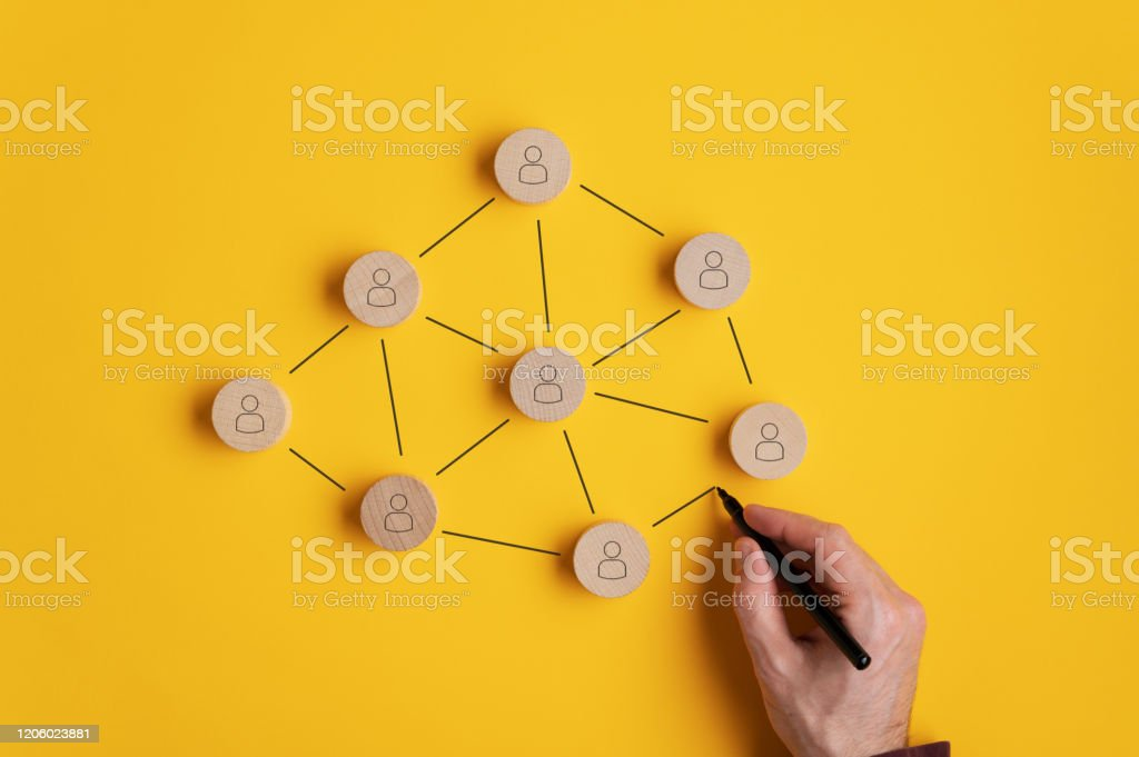 Conceptual image of network marketing Conceptual image of network marketing - male hand connecting the wooden cut circles with person icon on them. Business Stock Photo