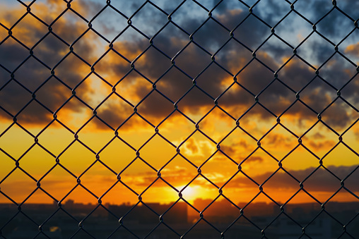 Conceptual image of sunrise sky and steel mesh wire fence. Concept of hope and freedom
