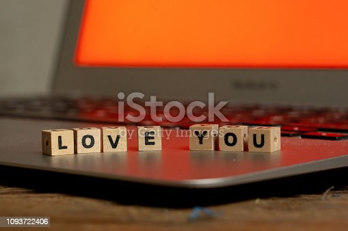 istock Conceptual image of text Love you in wood blocks on computer with mood romantic screen light background in Valentines day internet connection technology online dating and communication concept. 1093722406