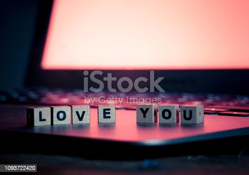 istock Conceptual image of text Love you in wood blocks on computer with mood romantic screen light background in Valentines day internet connection technology online dating and communication concept. 1093722420