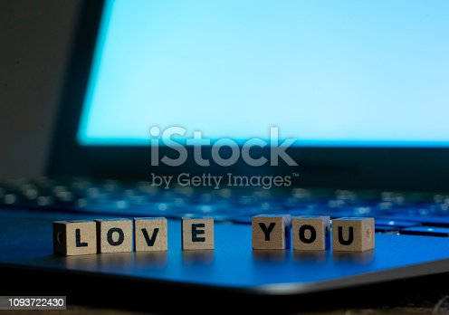 istock Conceptual image of text Love you in wood blocks on computer with mood romantic screen light background in Valentines day internet connection technology online dating and communication concept. 1093722430
