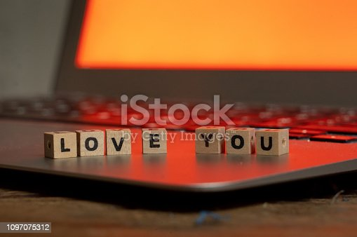 istock Conceptual image of text Love you in wood blocks on computer with mood romantic screen light background in Valentines day internet connection technology online dating and communication concept. 1097075312
