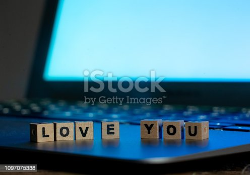 istock Conceptual image of text Love you in wood blocks on computer with mood romantic screen light background in Valentines day internet connection technology online dating and communication concept. 1097075338
