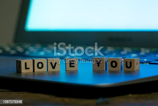 istock Conceptual image of text Love you in wood blocks on computer with mood romantic screen light background in Valentines day internet connection technology online dating and communication concept. 1097075348