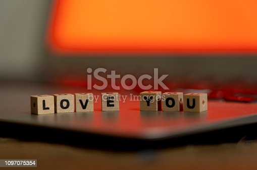 istock Conceptual image of text Love you in wood blocks on computer with mood romantic screen light background in Valentines day internet connection technology online dating and communication concept. 1097075354