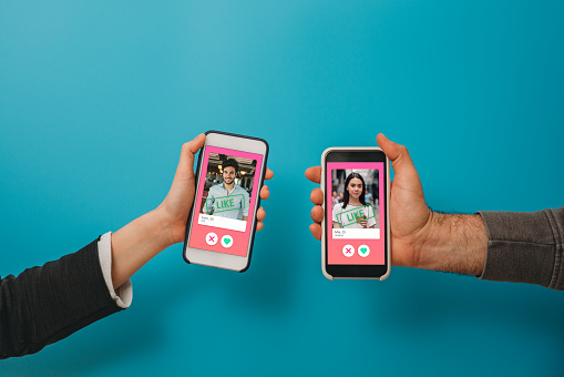 Conceptual image of two hands holding smart phones with an online dating app on the screen. Online dating app concept. Blue background.