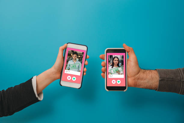 Conceptual image of two hands holding smart phones with an online dating app on the screen stock photo