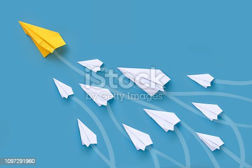 Origami paper airplane in group flying upwards lead by a bigger yellow paper airplane.