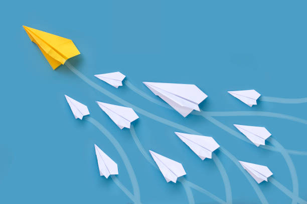 Conceptual leadership image. Origami paper airplane in group flying upwards lead by a bigger yellow paper airplane. paper airplane stock pictures, royalty-free photos & images