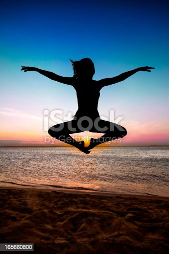 Woman levitating in a Lotus like position on mid-air at sunrise or sunset