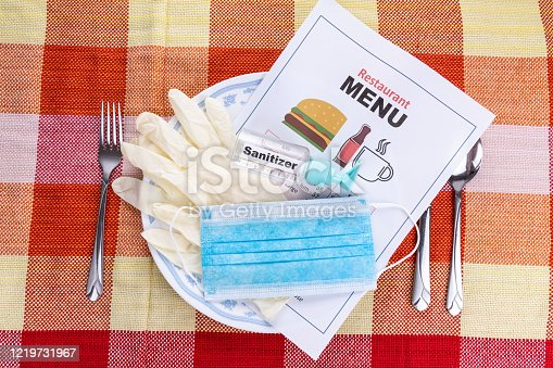 Conceptual of the new normal lifestyle with usage of sanitizer, face mask, gloves and disposable menu at restaurant dining table