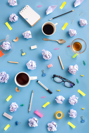 Stylised messy brainstorming working table top view with stationaries and coffee cup.