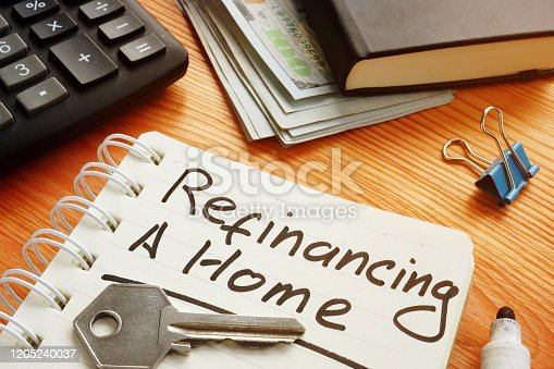 Conceptual photo is showing printed text refinancing a home