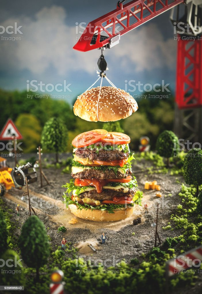 Conceptual photo of a very large burger on a construction site. stock photo