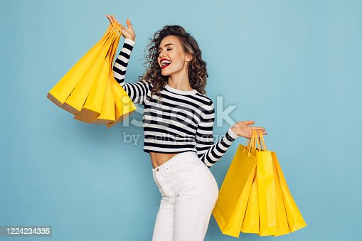 Conceptual photo of happy girl holds shopping packages on blue background