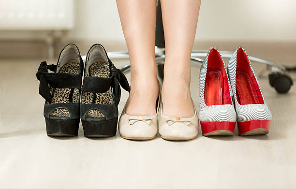 conceptual photo of woman choosing most comfortable shoes - flat shoe stock photos and pictures