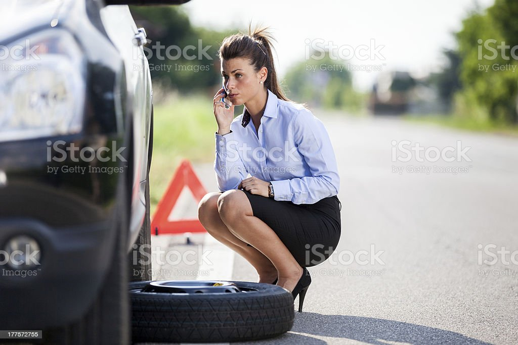 Conceptual photo of woman with a flat tire stock photo
