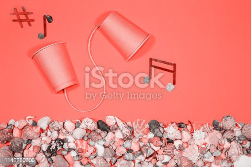 Conceptual picture in color of the year 2019, earphones and musical notes. Seashells and snails