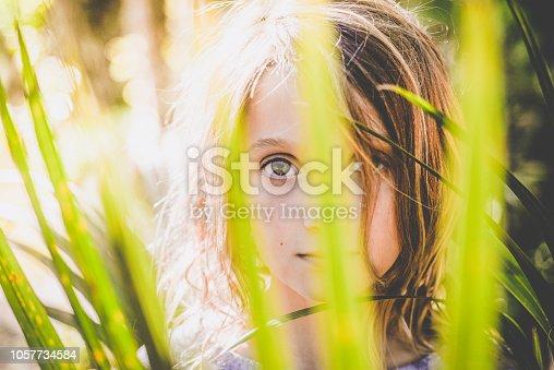 A child peeks through some tropical foliage, creative portrait