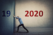 istock Conceptual scene as a confident person pushing the 2019 old wall to make space for the coming new 2020 year. Determined guy announcing a new start, ready for change and challenges. 1191509950