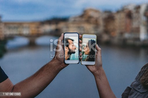 Conceptual shot of a young adult couple kissing via mobile phone