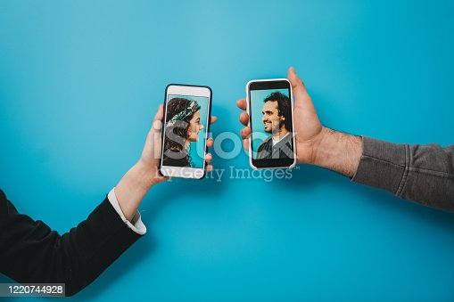 Conceptual shot of a young couple connecting together with a smartphone during social distancing. They are holding smart phones against a blue background.