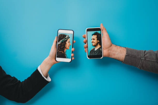 Conceptual shot of a young couple connecting together with a smartphone during social distancing stock photo