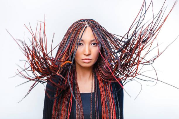 konzeptuelle studioaufnahme einer modernen kreativen frau mit bunten geflochtenen dreads - rote dreads stock-fotos und bilder