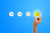 istock Conceptual the customer responded to the survey. The client using hand choose happy face smile icon on blue background.Depicts that customer is very satisfied. Service experience satisfaction concept. 1163375088