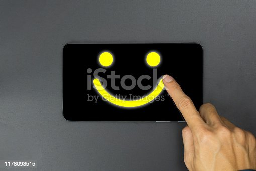 693589426 istock photo Conceptual the customer responded to the survey. The client using hand write happy face smile icon on tablet. Depicts that customer is very satisfied. Service experience and satisfaction concept. 1178093515