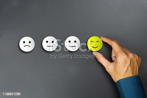 693589426 istock photo Conceptual the customer responded to the survey. The client using hand choose happy face smile icon. Depicts that customer is very satisfied. Service experience and satisfaction concept. 1188641295