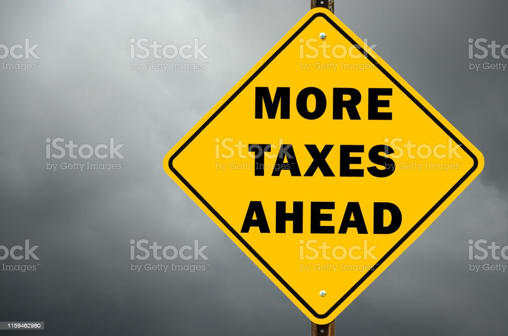 More taxes ahead conceptual road sign with stormy sky in background
