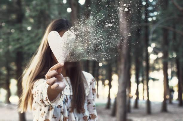 conceptuele vrouw portret met dispersie als gevolg van een hart in haar hand - liefdesverdriet stockfoto's en -beelden
