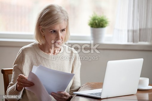 istock Concerned aged female managing bank documents working at laptop 1070069212