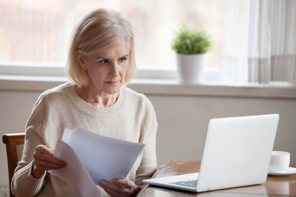 Concerned aged female managing bank documents working at laptop picture id1070069212?b=1&k=6&m=1070069212&s=612x612&w=0&h=c3fnxbpgbngjigpq9kpqpuenedinsov4qrk6wn9xmrw=