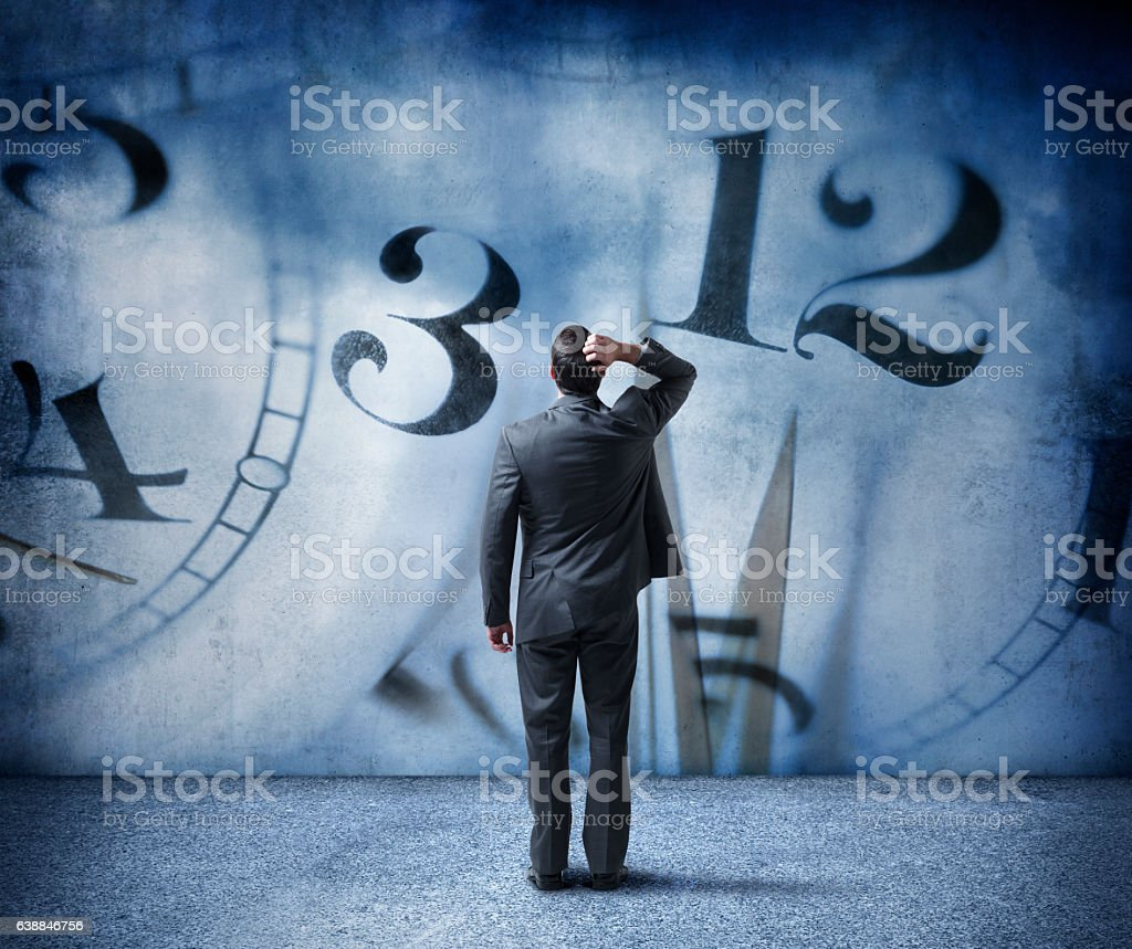Concerned Businessman Looks Up At Symbols Of Time stock photo