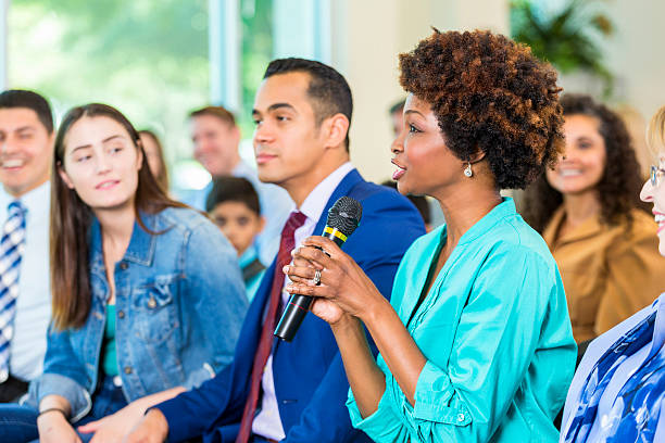 Concerned constituent asks politician a question during meeting Beautiful African American woman holds a microphone and asks a mayoral candidate a question during a political meeting. Diverse citizens are in the audience with her. local government building stock pictures, royalty-free photos & images