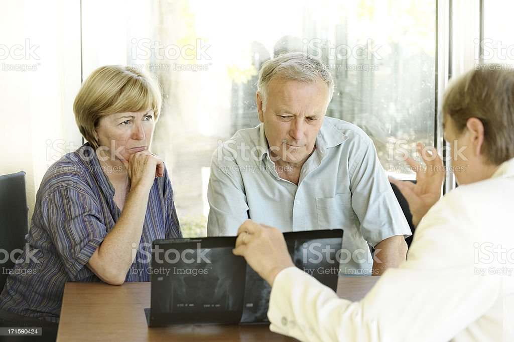 Concerned couple see X-rays with specialist royalty-free stock photo