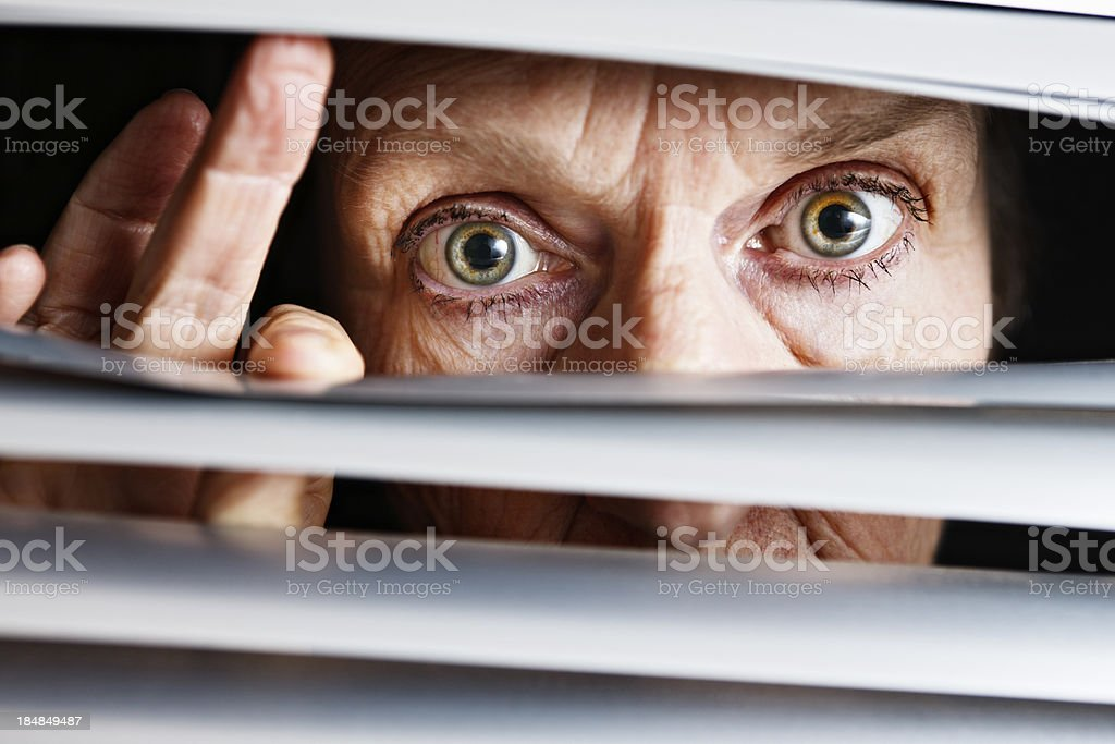 Concerned curious old woman looks through venetian blinds stock photo