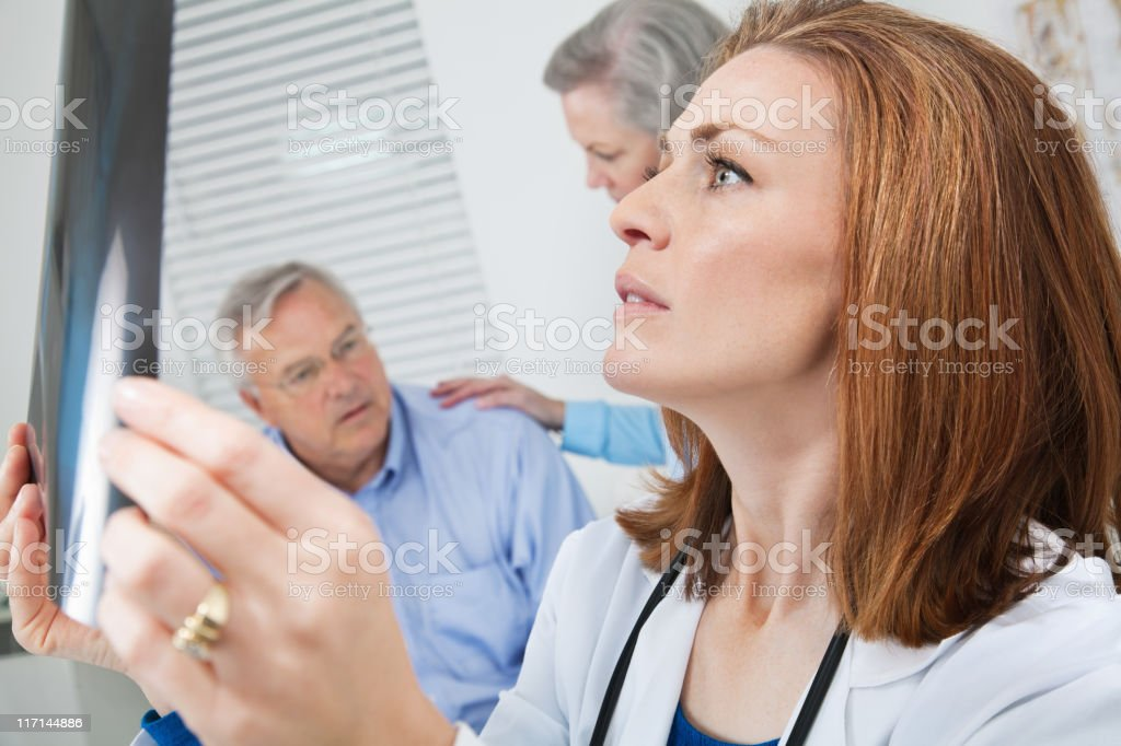 Concerned Doctor Examining X-Ray With Patient Behind Her royalty-free stock photo