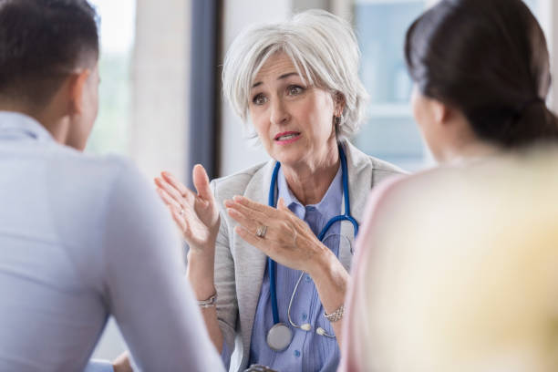concerned doctor has serious conversation with patient - infertility stock pictures, royalty-free photos & images